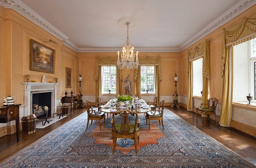 The formal dining room has a sunny beige tone to its walls that pair well with the white molding and white ceiling. The white molding blends well with the mantle of the fireplace on the side of the dining set. Image courtesy of Toptenrealestatedeals.com.