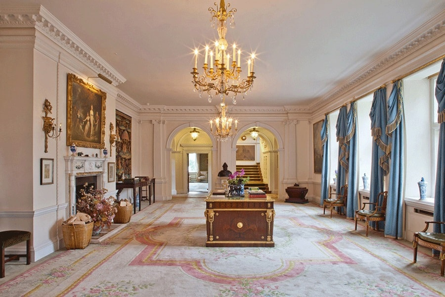 This is a spacious and luxurious foyer with a couple of golden chandeliers hanging from the beige ceiling over a dark wooden table in the middle that has golden accents. Image courtesy of Toptenrealestatedeals.com.