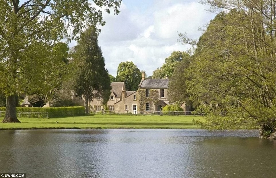 The property also has a large pond that can be seen from the house. It is surrounded by large grass lawns and tall trees. Image courtesy of Toptenrealestatedeals.com.