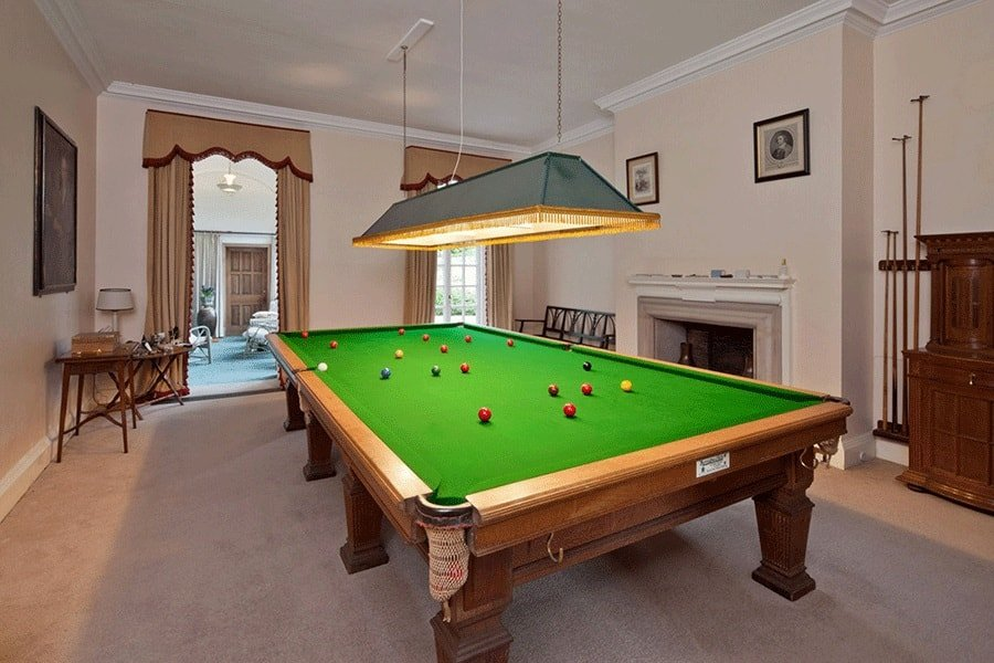 The game room has a large wooden pool table illuminated by a rectangular pendant light. On the side is its own fireplace embedded into the wall that has a light pastel hue. Image courtesy of Toptenrealestatedeals.com.