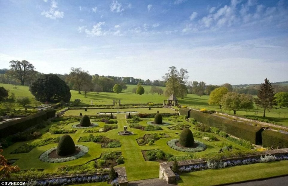 This is the other garden of the property with well-maintained shrubs in decorative shapes and borders of waist-high shrubs on the side. Image courtesy of Toptenrealestatedeals.com.
