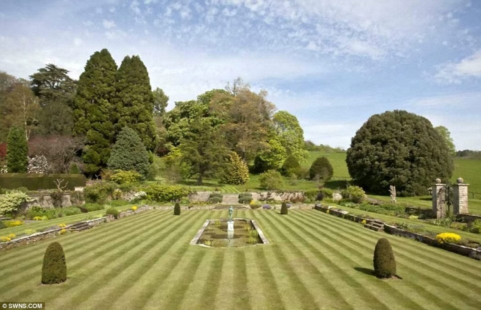 This is the well-maintained and well-manicured lawn with tall trees and thick shrubs in the background as well as lining the borders. Image courtesy of Toptenrealestatedeals.com.