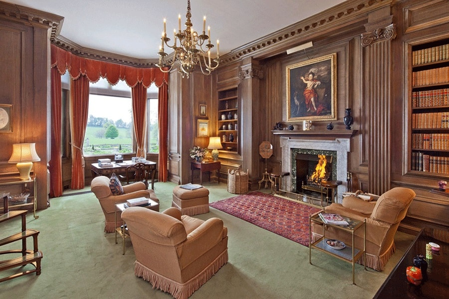 The library has green carpeting on its floor that matches well with the wooden tone of the walls that has built-in bookshelves on each side of the fireplace. Image courtesy of Toptenrealestatedeals.com.