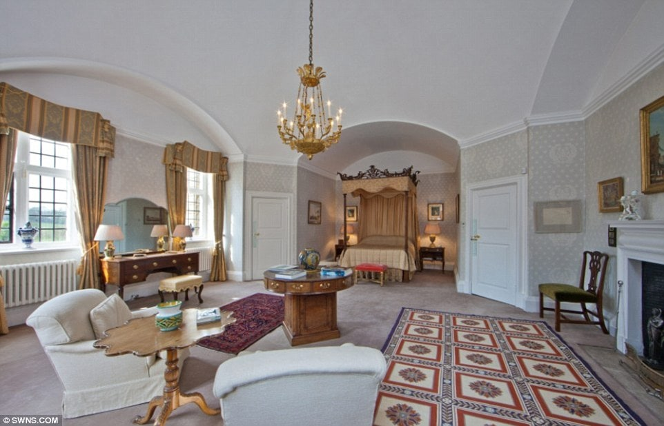 This is the primary bedroom with a four-poster bed on the far side within an alcove. It has a large central area with a chandelier hanging from the white cove ceiling. Image courtesy of Toptenrealestatedeals.com.