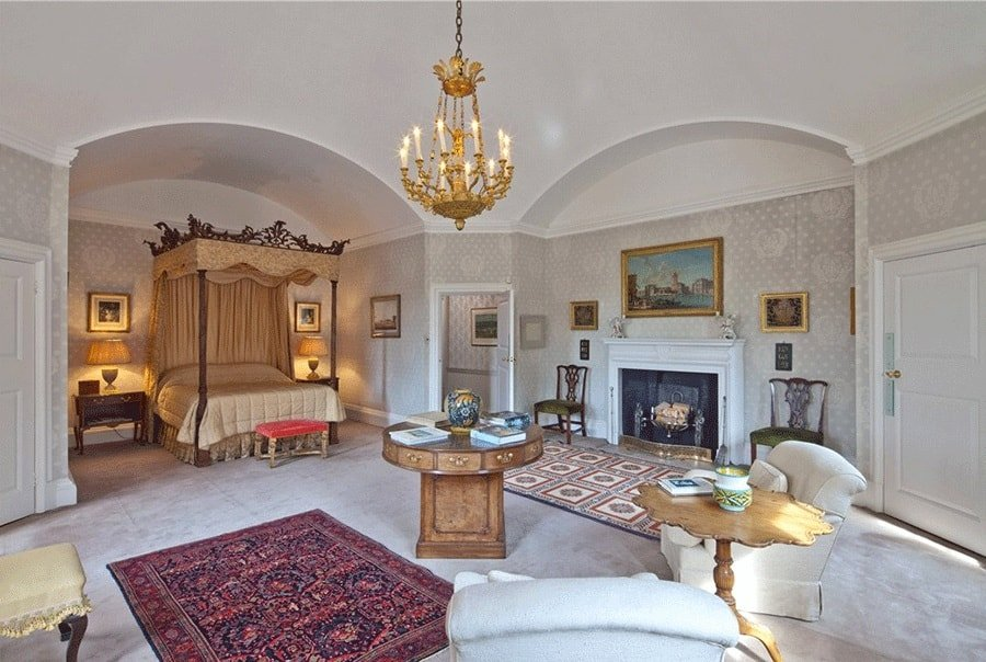 This other angle of the primary bedroom shows the fireplace on the side with a white mantle topped by a colorful painting within an alcove that matches that of the bed. Image courtesy of Toptenrealestatedeals.com.
