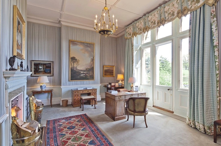 This is a spacious home office with a fireplace on the side, a large window on the other side and a wooden desk in the middle beneath a golden chandelier. Image courtesy of Toptenrealestatedeals.com.