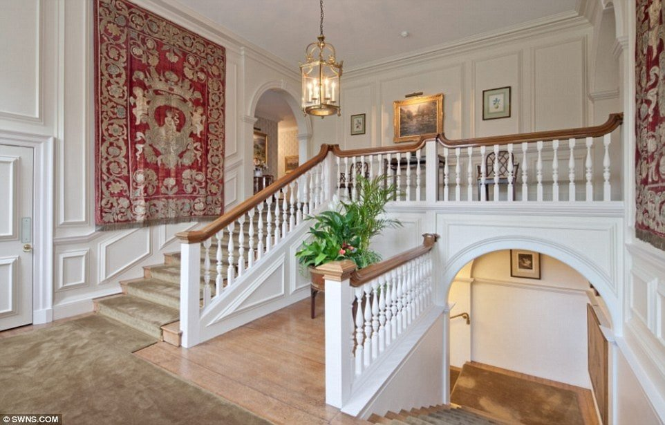 This is a view of the staircase with white wooden railings adorned with a potted plant, a pendant light and a colorful patterned tapestry mounted on the wall. Image courtesy of Toptenrealestatedeals.com.