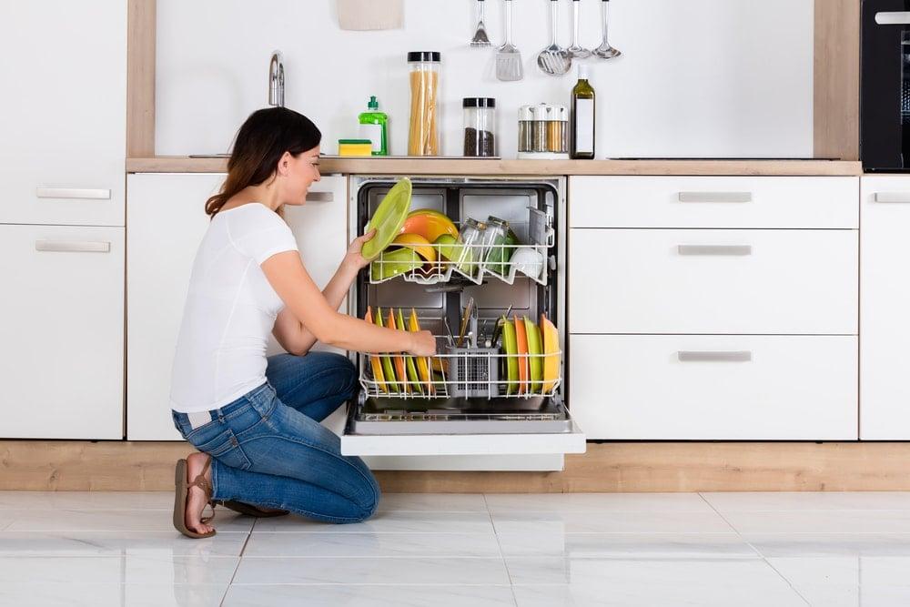 Bir kadın bulaşık makinesinden temiz bulaşıkları çıkarmak için diz çöker.