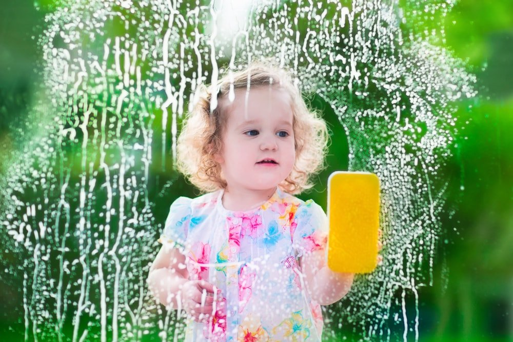 A child cleaning the glass window with a sponge.