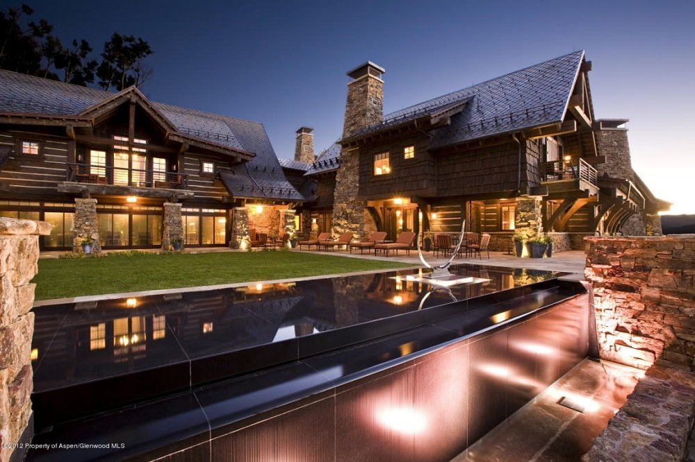 This is a view of the mansion showcasing its rustic flair and warm lighting that emanates from large glass windows. Here you can also see the towering stone chimneys and comfortable outdoor areas on the side of the house. Image courtesy of Toptenrealestatedeals.com.