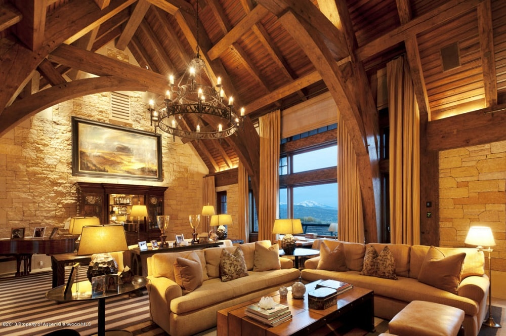 The living room has a tall wooden cathedral ceiling with exposed beams and a large circular chandelier hanging over the sofas. Image courtesy of Toptenrealestatedeals.com.