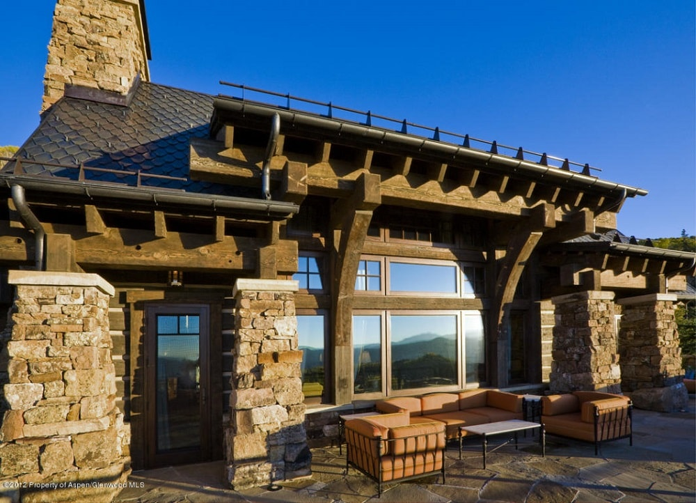 This is a close look at the side of the house with large glass windows adorned by thick stone pillars. You can see here the patio that was fitted with outdoor furniture with brown cushions. Image courtesy of Toptenrealestatedeals.com.