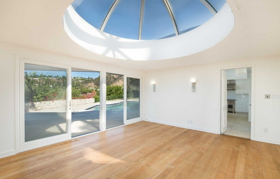 An empty room with glass doors and a custom skylight ceiling, along with hardwood floors and white walls. Image courtesy of Toptenrealestatedeals.com.