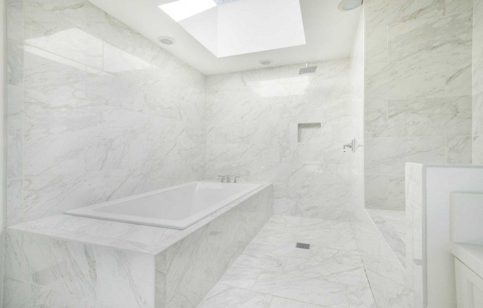 Primary bathroom with gorgeous tiles flooring and walls, along with a ceiling featuring a skylight. Image courtesy of Toptenrealestatedeals.com.