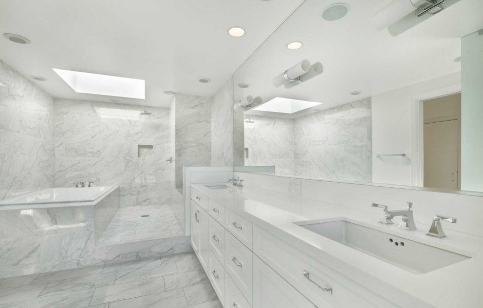 Bright primary bathroom featuring a drop-in soaking tub and an open shower. Image courtesy of Toptenrealestatedeals.com.