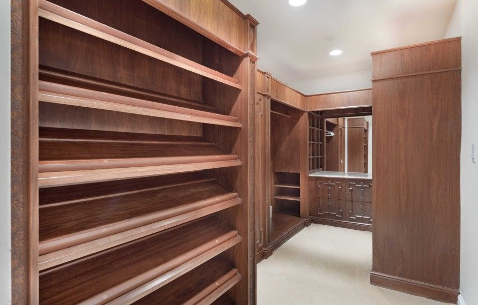 Walk-in closet with brown cabinets and shelving, along with a counter and mirror. Image courtesy of Toptenrealestatedeals.com.