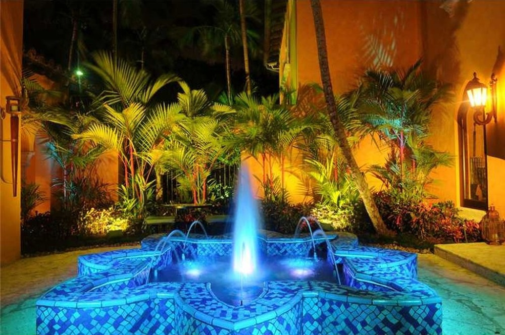 Focused look on the home's stunning fountain landscape design with blue lighting. Image courtesy of Toptenrealestatedeals.com.