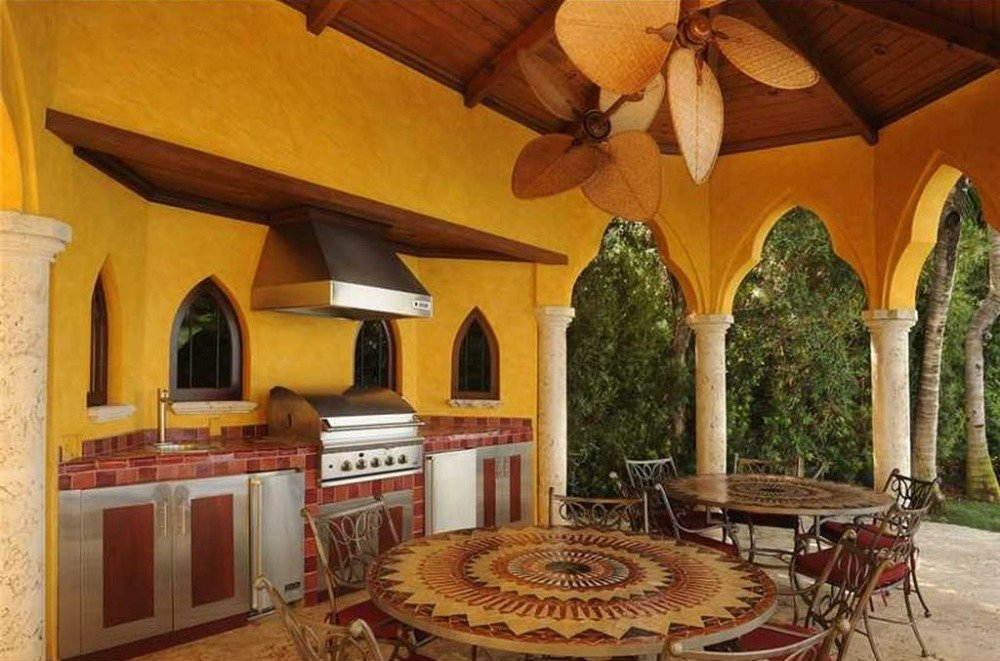Outdoor dining and kitchen with two sets of table and chairs. Image courtesy of Toptenrealestatedeals.com.