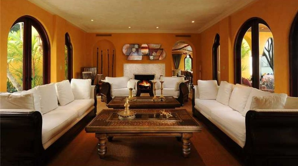 Living room with a classy sofa set along with a couple of center tables and a fireplace. Image courtesy of Toptenrealestatedeals.com.