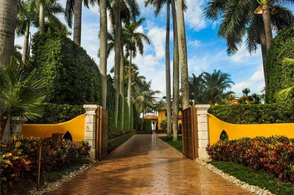 Entry gate of the house surrounded by landscaping plants and trees. Image courtesy of Toptenrealestatedeals.com.