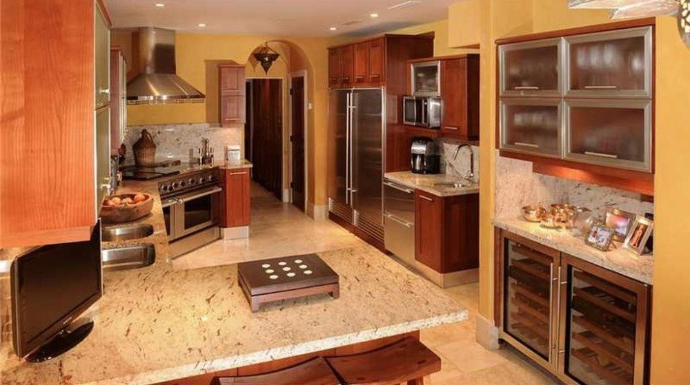 Kitchen with a gorgeous marble contertop and brown built-in cabinetry. Image courtesy of Toptenrealestatedeals.com.