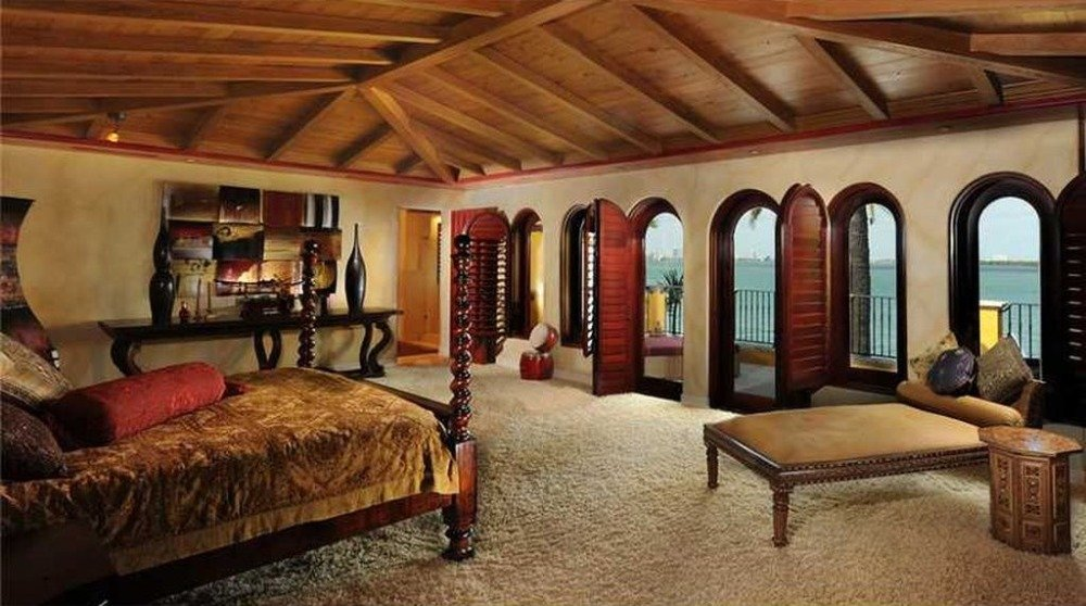 Primary bedroom suite with an elegant bed set and carpeted flooring. The room also has a personal bathroom. Image courtesy of Toptenrealestatedeals.com.