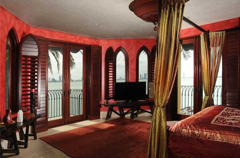 This bedroom features red walls and a cozy bed set, along with a TV on the side. Image courtesy of Toptenrealestatedeals.com.