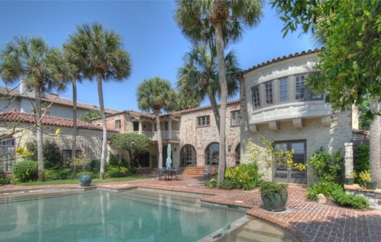 This is a closer look at the back of the house. Here you can see that it has arches, textured exterior walls and tall tropical trees that bring vibrancy to it. Image courtesy of Toptenrealestatedeals.com.