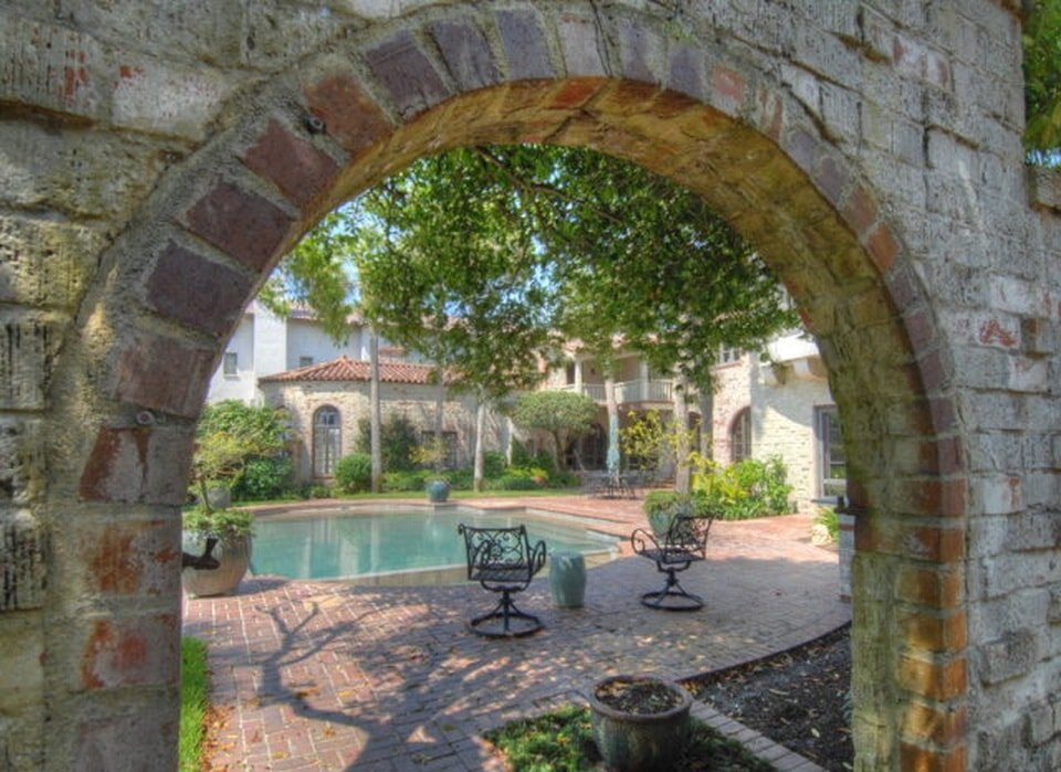There is a red brick archway that leads to the backyard swimming pool. Here you can see that the poolside area has earthy terracotta walkways fitted with outdoor chairs under the shade of the trees. Image courtesy of Toptenrealestatedeals.com.