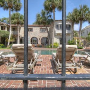 This is a look at the back of the house from outside the wrought-iron fence. You can see here the earthy textured exterior walls of the house adorned with tall tropical trees and a large swimming pool surrounded by terracotta-brick walkways. Image courtesy of Toptenrealestatedeals.com.