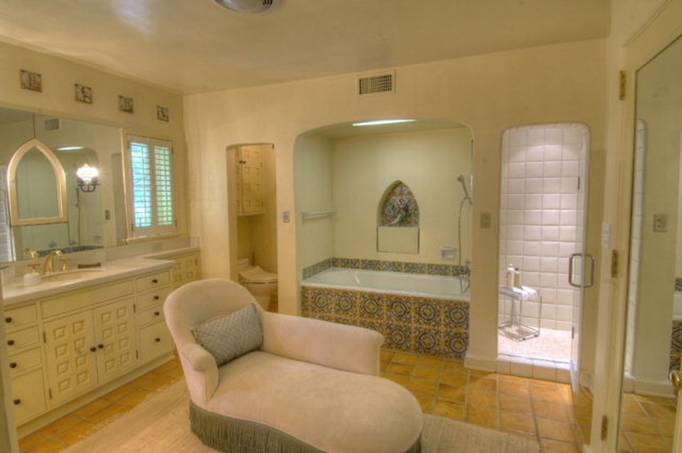 The primary bathroom has consistent beige hues on its walls, ceiling and flooring tiles to match the vanity. There is also a bathtub with its own alcove beside the entrance to the walk-in shower. Image courtesy of Toptenrealestatedeals.com.