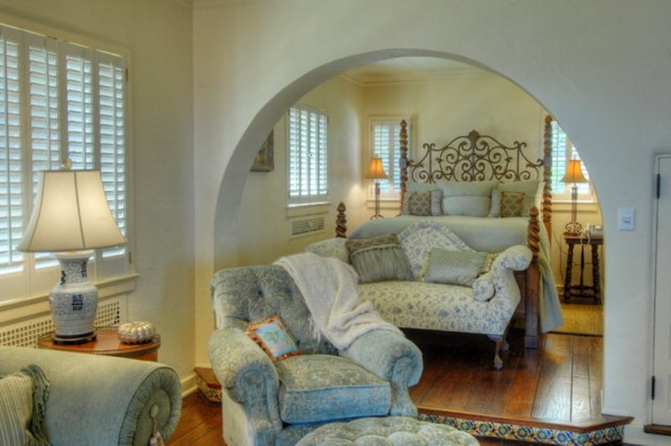 The primary bedroom has a large bed placed inside an alcove with an archway leading to the sitting area that has cushioned armchairs. Image courtesy of Toptenrealestatedeals.com.
