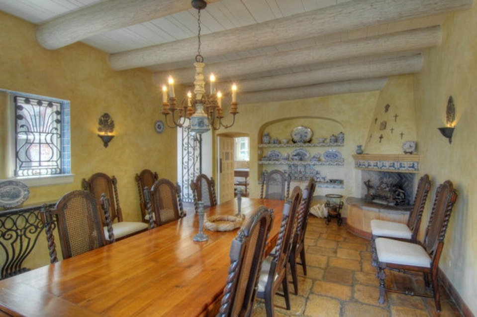 This is the formal dining room with a large wooden dining table surrounded by wooden chairs and topped with a chandelier hanging from the white ceiling with exposed beams. Image courtesy of Toptenrealestatedeals.com.