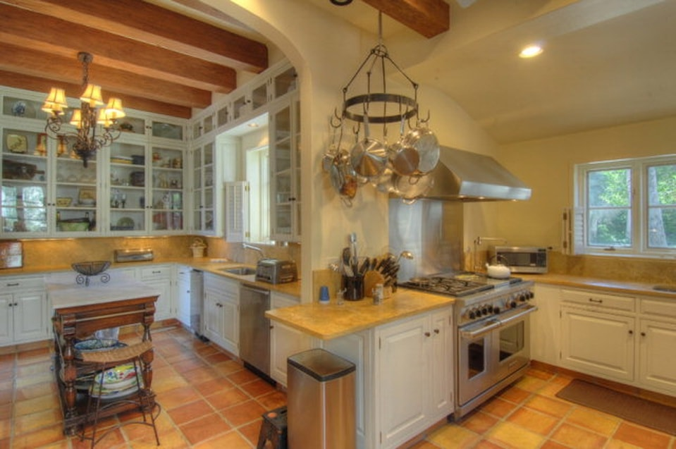 This large kitchen has beige walls to match the beige ceiling with exposed wooden beams. These elements make the stainless steel appliances stand out as well as the earthy beige tiles of the floor. Image courtesy of Toptenrealestatedeals.com.