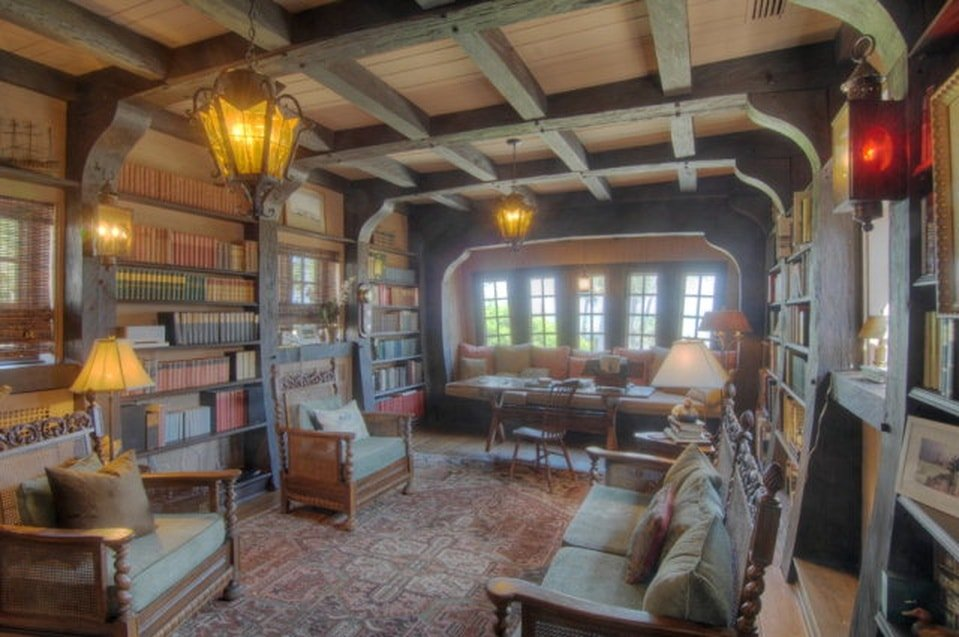 This is the spacious library of the house with built-in wooden shelves on the walls, a wooden ceiling with exposed beams and decorative pendant lights and a reading nook at the far end under the window. Image courtesy of Toptenrealestatedeals.com.