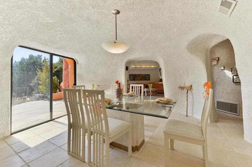 The dining room has curved walls that blend into the ceiling that hangs a pendant light over the glass-top dining table. Image courtesy of Toptenrealestatedeals.com.