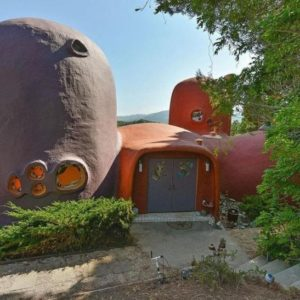 This is the front view of this unique free-form house that has purple and tangerine exterior walls extending to curved roofs. These are then complemented by irregular window shapes and green landscaping. Image courtesy of Toptenrealestatedeals.com.