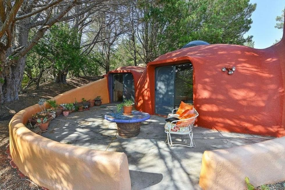 This side of the house is fitted with an outdoor patio under the shade of the tall trees. It has a couple of outdoor armchairs and a round coffee table standing a concrete floor that makes the tangerine exterior walls stand out. Image courtesy of Toptenrealestatedeals.com.