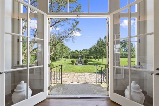 This is a look at the main entrance from inside the foyer. Here you can see the glass doors surrounded by glass panels to give a wide view of the landscape beyond. Image courtesy of Toptenrealestatedeals.com.
