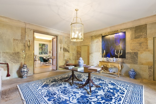 This is the spacious foyer that has a large blue patterned area rug in the middle topped with a wooden table and a drum pendant light from the white ceiling. Image courtesy of Toptenrealestatedeals.com.