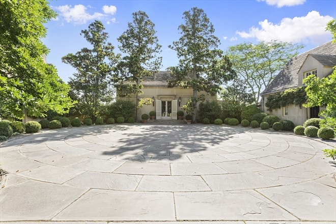 This is a view of the front of the house with a large circular courtyard that is lined on the sides with shrubs and trees leading to the main entrance of the house on the far side. Image courtesy of Toptenrealestatedeals.com.