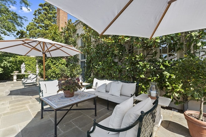 This is the patio of the house fitted with wrought iron sofas and armchairs shaded by the large umbrellas. This area is adorned with creeping plants on the walls that serve as background. Image courtesy of Toptenrealestatedeals.com.