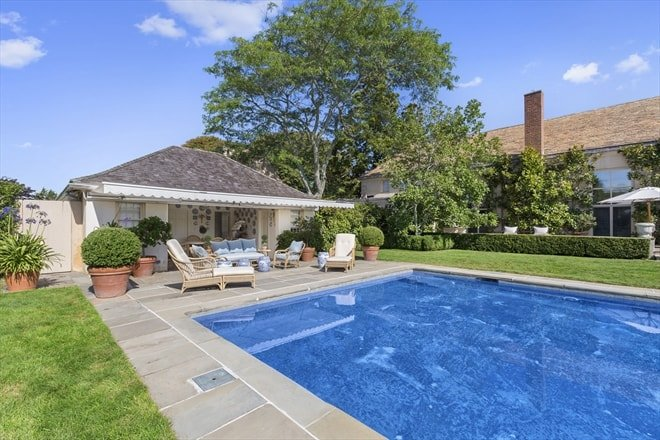 This is the backyard pool of the house surrounded by lawns of grass. On the far side you can see the pool house that has a sitting area beside it for those who want to relax beside the pool. Image courtesy of Toptenrealestatedeals.com.