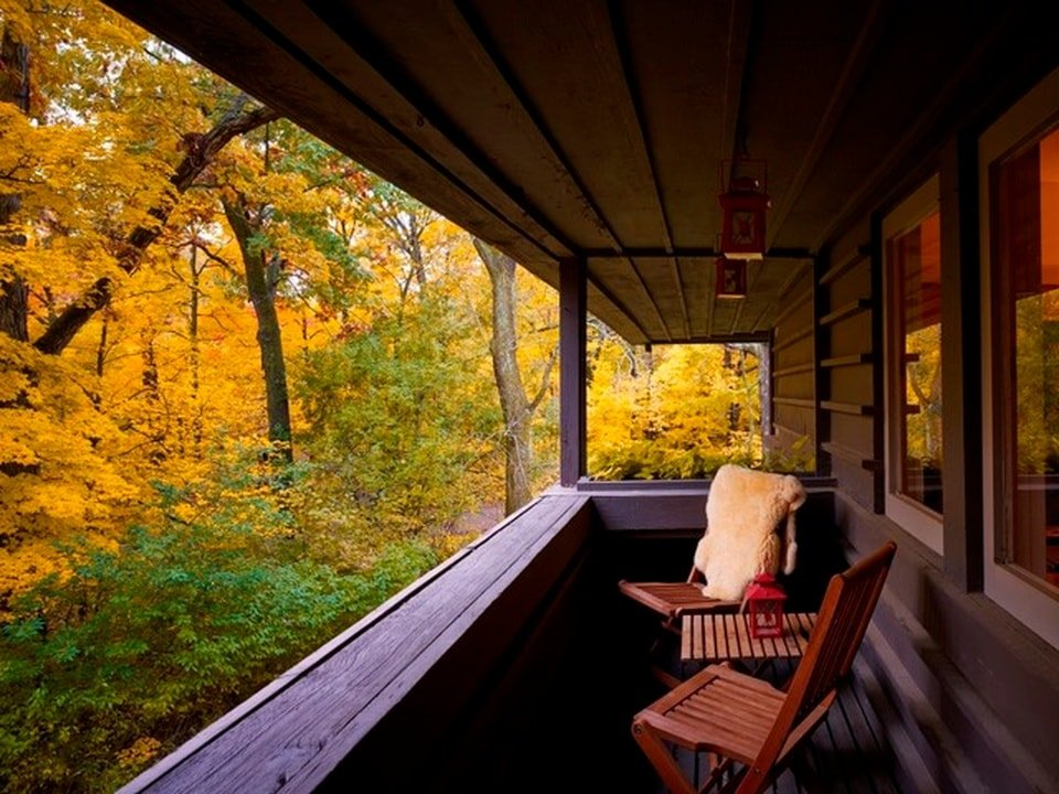 This is a long and narrow balcony fitted with a couple of wooden chairs and a small side table to better enjoy the scenery. Image courtesy of Toptenrealestatedeals.com.