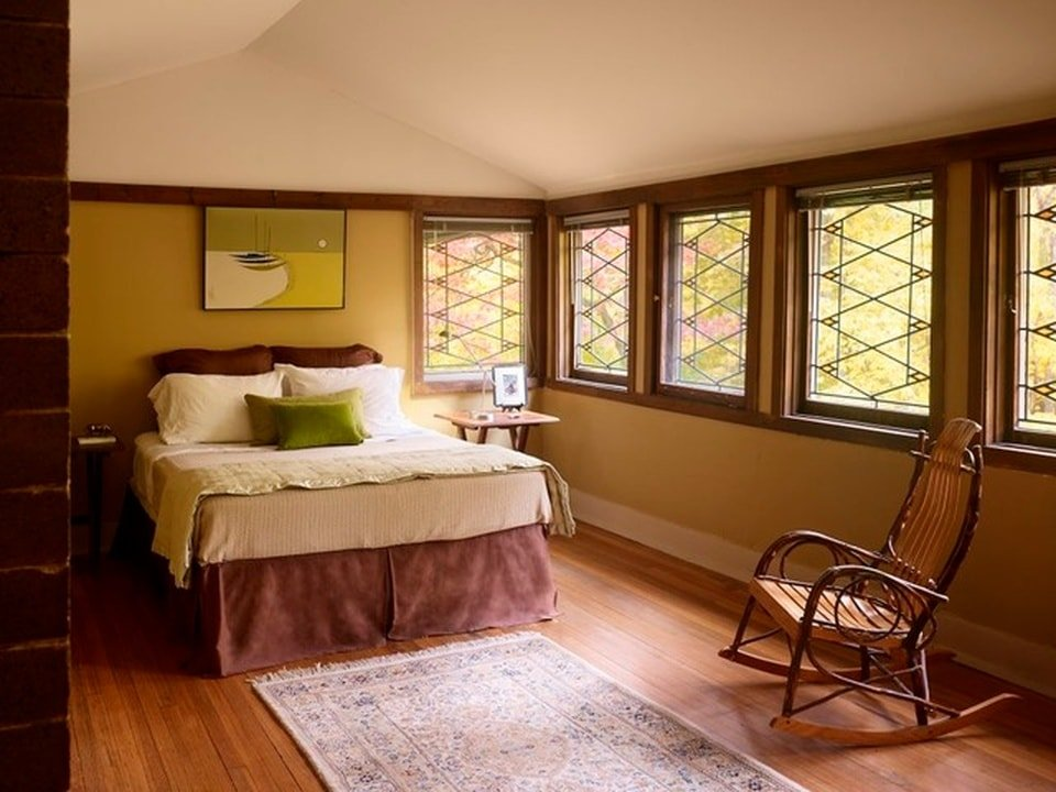 The bedroom has a white cathedral ceiling to contrast the dark wooden accents of the beige walls and the bed with a rocking chair by the window. Image courtesy of Toptenrealestatedeals.com.