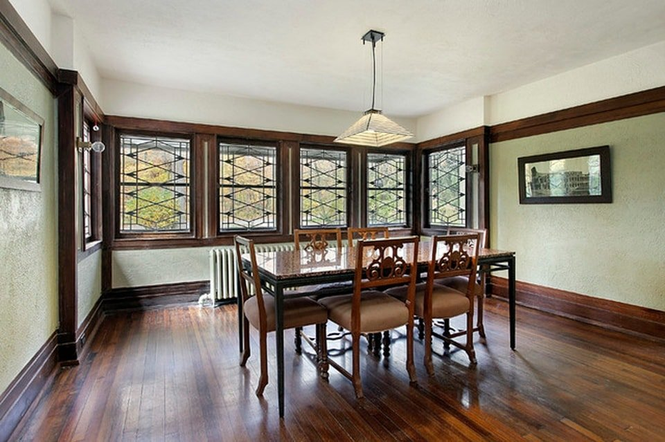 The dining room has a row of windows with dark wooden frames that match with the dining table and its chairs. Image courtesy of Toptenrealestatedeals.com.
