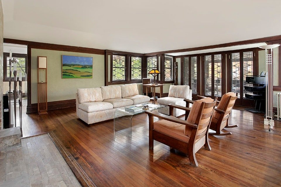 The living room has a dark hardwood flooring that contrasts the beige L-shaped sectional sofa. The flooring matches with the dark wooden molding and the frames of the windows and doors. Image courtesy of Toptenrealestatedeals.com.
