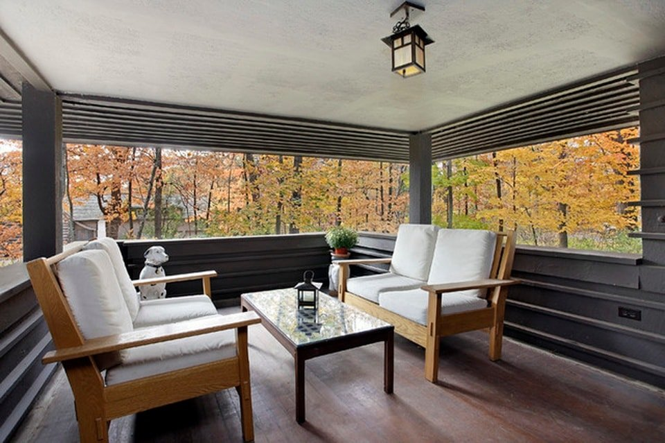 This is the covered patio of the house fitted with a couple of wooden two-seater sofas with white cushions and a clear view of the surrounding landscape. Image courtesy of Toptenrealestatedeals.com.