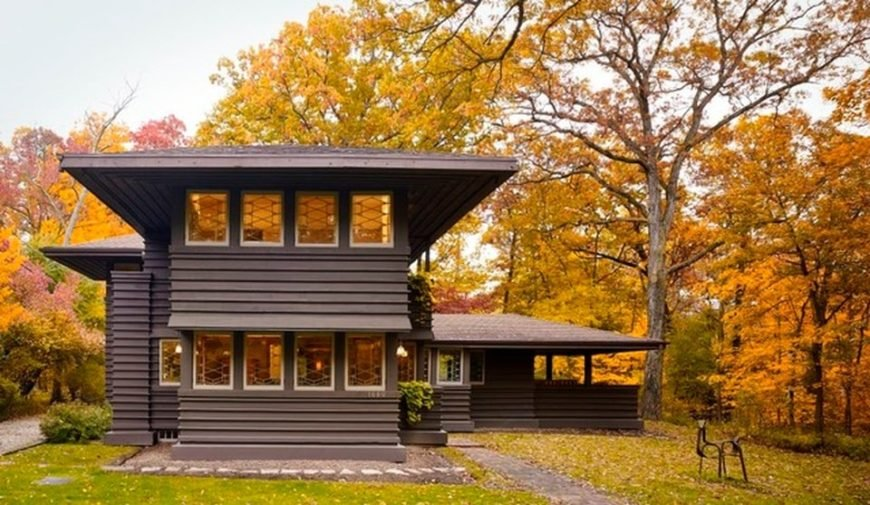 This is a look at the side of the house. Here you can appreciate the dark brown tone of the house exterior lined with warm, glowing rows of windows. These are then complemented by the surrounding mature trees. Image courtesy of Toptenrealestatedeals.com.