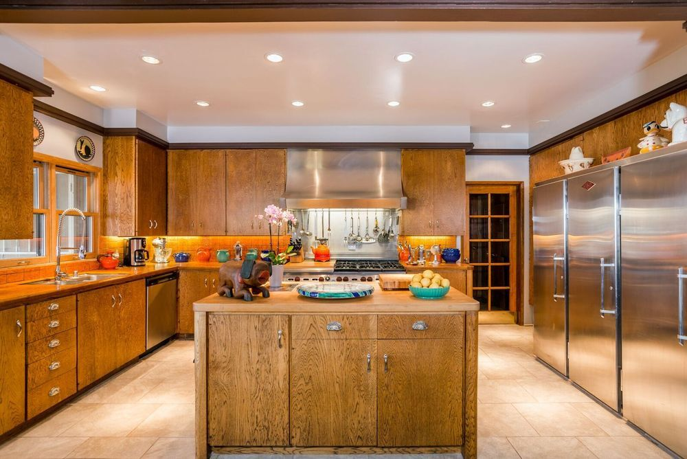 Another look at the kitchen showcasing its brown cabinetry and kitchen counter matching the brown center island. Image courtesy of Toptenrealestatedeals.com.